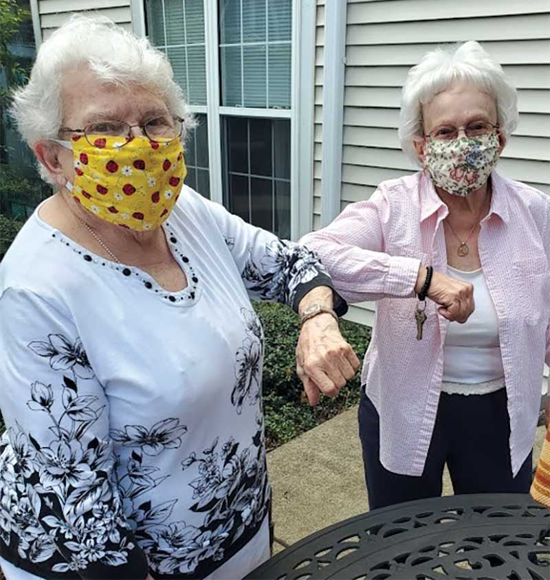 Senior ladies wearing covid masks and elbow bumping